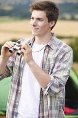 Young Man With Binoculars On Camping Trip