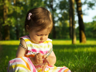 Adorable Baby Girl playing with beads