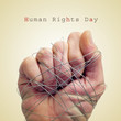 man hand tied with wire and the text human rights day