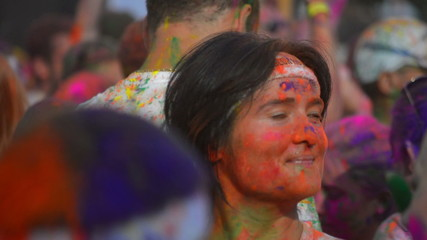 young woman covered in orange dye dances at party