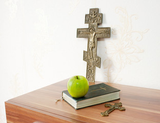 holy bible with green apple and two crosses
