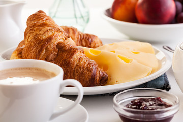 Croissants with cheese, fruits and coffee