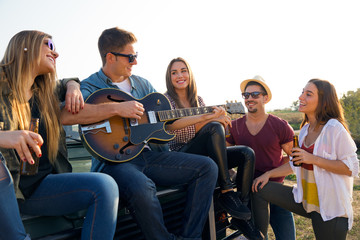 Portrait of group of friends playing guitar and drinking beer.