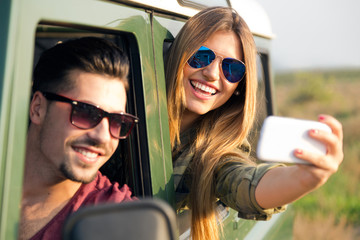 Portrait of pretty couple taking selfie with smartphone in the c