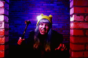 Portrait of funny zombie girl in halloween time with hammer