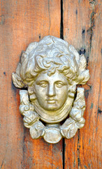 old wooden door with a bronze head and iron rivets