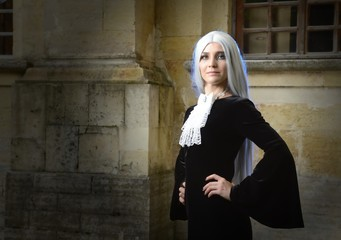 Beautiful woman in Gothic style with long blond hair near church