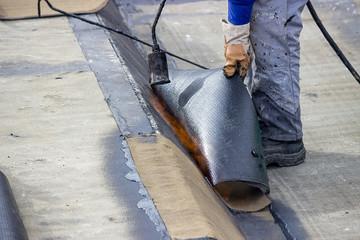 Worker heating and melting bitumen felt 2