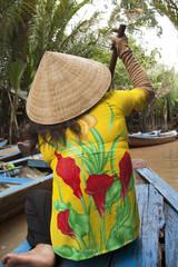 Vietnamese woman paddles a boat in Mekong River in Vietnam