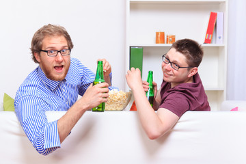 Two guys with beer and popcorn on the sofa
