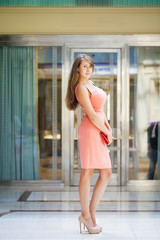 Young woman in pink dress walking in the shop