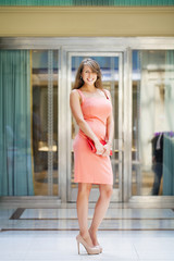 Beautiful woman in pink dress in the shop