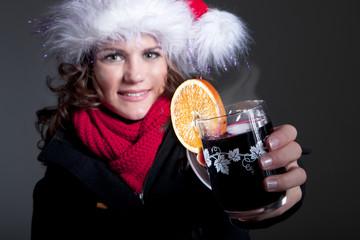 Junge freundliche Frau mit Weihnachtsmütze und heißem Glühwein