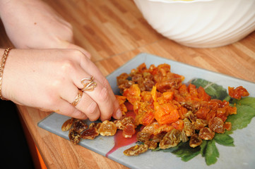 Woman hands cooking with dried fruits
