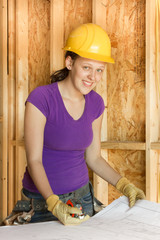 Woman construction looking over architectural drawings