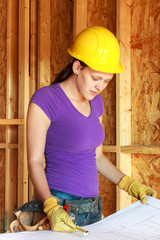 Woman in hardhat looking over architectural drawings