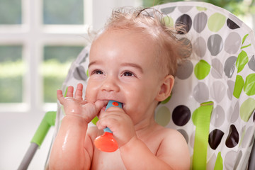 Funny smiling ragged baby holding spoon in mouth