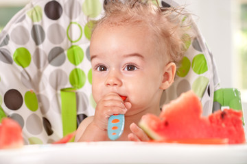 Ragged baby holding spoon itself and eating watermelon