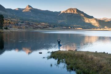Yoga at mountain lake view in sunset, colorado