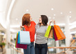 two smiling teenage girls with shopping bags