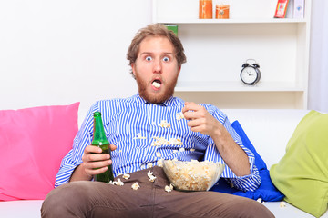 Surprised man eating popcorn on the sofa