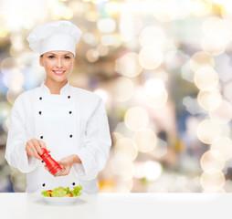 smiling female chef spicing vegetable salad