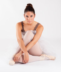 ballet dancer sitting on white studio floor