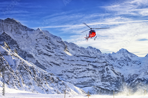 Red helicopter flying at swiss alps near Jungfrau mountain - 73182957
