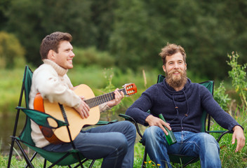 smiling tourists playing guitar in camping
