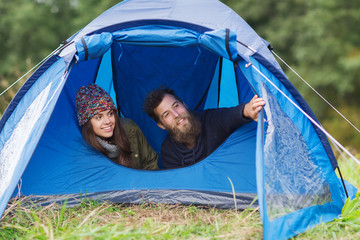 smiling couple of tourists looking out from tent