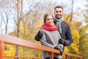 smiling couple hugging on bridge in autumn park