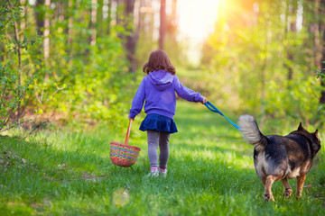 Little girl walking with dog in the forest