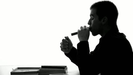 Silhouette of a young man or businessman smoking a Cuban cigar