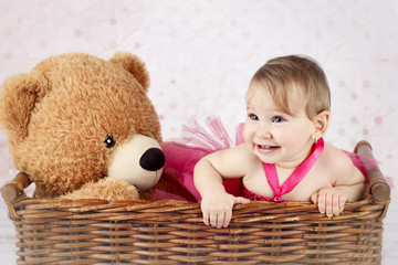Beautiful little girl with big teddy bear in the wicker basket