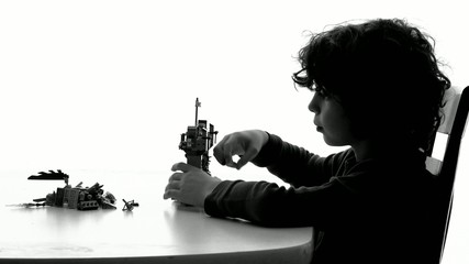 Silhouette of young child playing with plastic toys