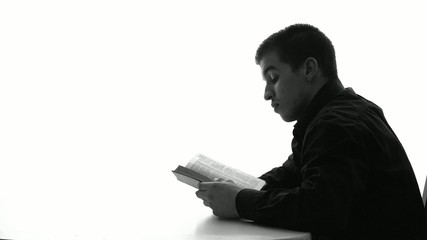 Silhouette of young man reading Bible and praying