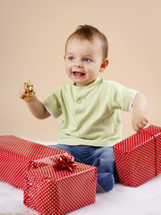 Little baby boy unwrapping christmas presents