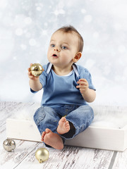 Little baby boy with christmas balls
