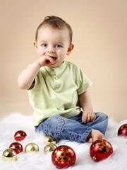 Happy little baby boy with christmas balls