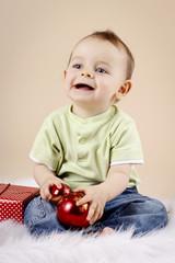 Little baby boy holding christmas balls