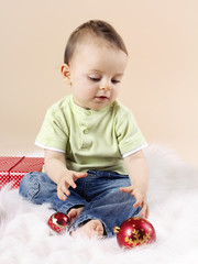 Little baby boy playing with christmas balls