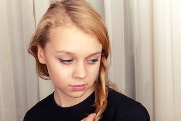 Blond Caucasian girl smiles shyly, closeup portrait