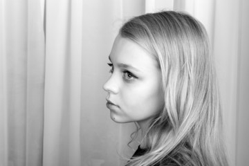 Serious blond Caucasian girl, monochrome portrait