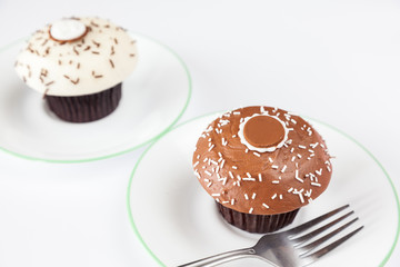 closeup chocolate cupcake with white sprinkle and fork