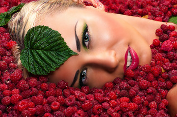 beautiful woman face in raspberries with leaves