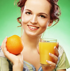 woman with orange juice over green background