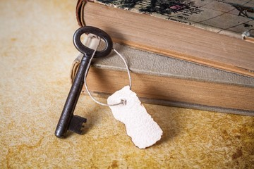 Old key with slip of paper and old books, on rustic paper