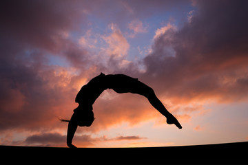 back handspring of female gymnast in sunset sky