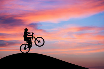 silhouetted mountainbiker doing wheelie in sunset sky on hill