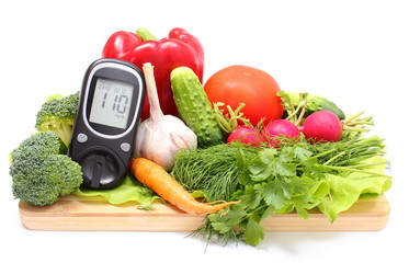 Glucose meter and fresh vegetables on wooden cutting board